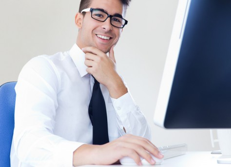 Portrait of happy young business man work in modern office on computer